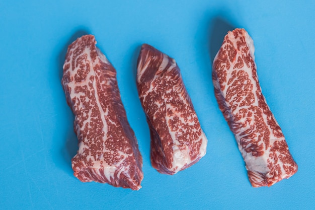 Beef pieces of raw meat on a blue background
