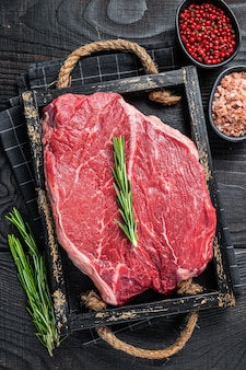 허브와 함께 나무 쟁반에 스테이크를 위한 쇠고기 생 필레. 검은 나무 배경. 평면도.