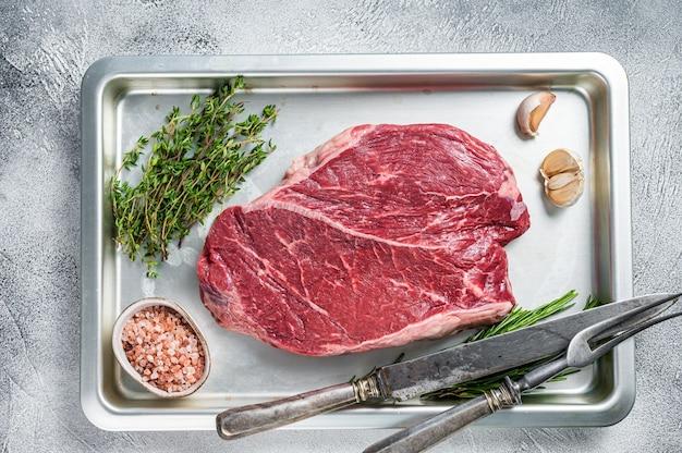 굽는 접시에 자른 쇠고기 생 스테이크. 흰색 배경. 평면도.