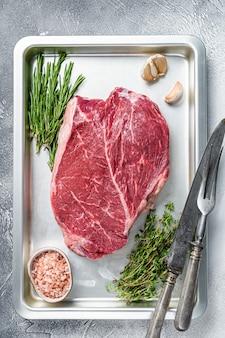 베이킹 접시에 자른 쇠고기 생 스테이크. 흰 바탕. 평면도.