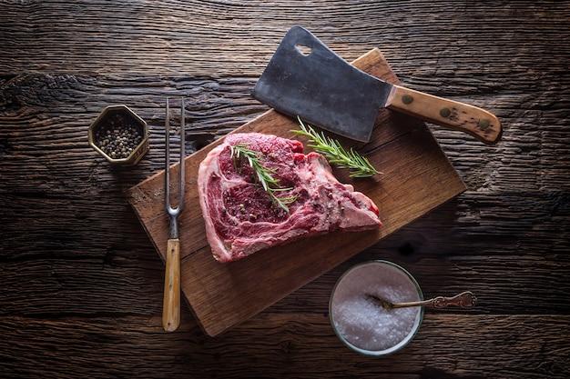 Сырой стейк из говядины. сырой свежий стейк на т-образной кости с соленым перцем и розмарином.
