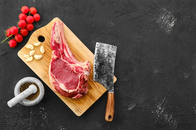 Beef ribeye steak with spices on wooden cutting board