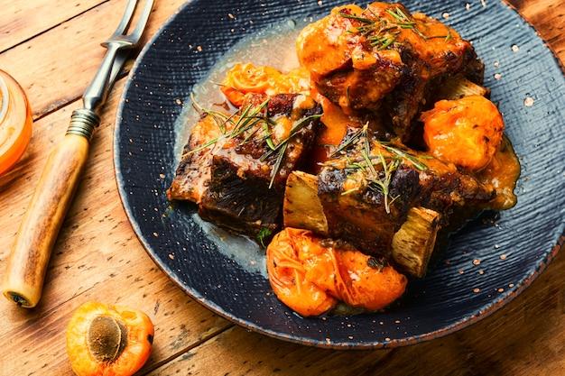살구에 조린 쇠고기 갈비. 소박한 나무 배경에 과일 소스를 곁들인 송아지 고기