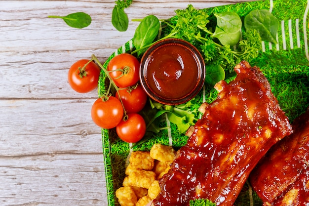 Beef ribs with barbecue sauce and vegetable on wooden board.