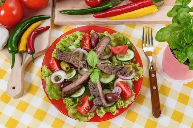 Салат из говядины на тарелке. мясо говядины на гриле с вкусным выбором овощей.