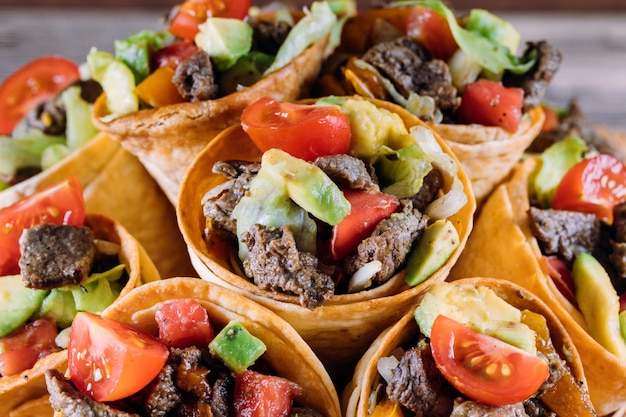 Beef salad in taco cones with pepper and avocado