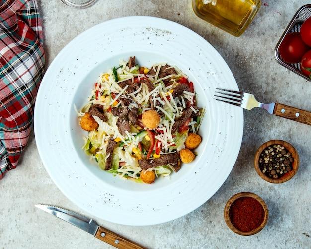 Салат из говядины с куриными шариками, листьями салата, тертым сыром, кукурузой и сладким перцем