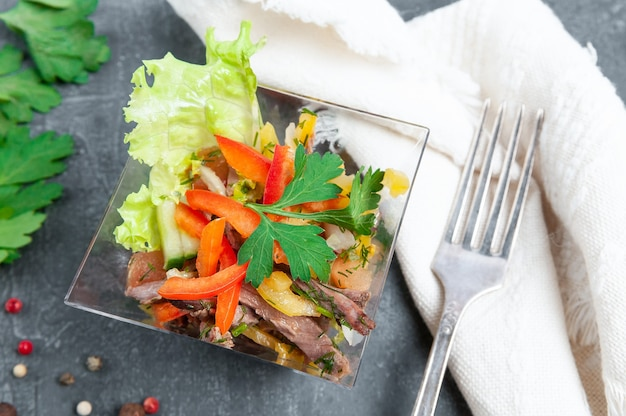 Beef salad with sweet pepper, cucumber and lettuce. in a square, glass plate. next to the plate is a white napkin and fork. view from above. dark background