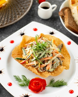 Beef salad with vegetables and mayonnaise served in flatbread crust