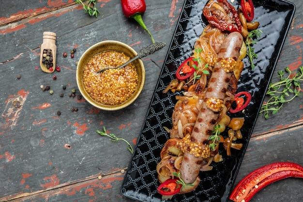 Колбаски из говядины и картофельные дольки подаются с перцем чили и горчицей на деревянном фоне. баннер, меню, место рецепта для текста, вид сверху