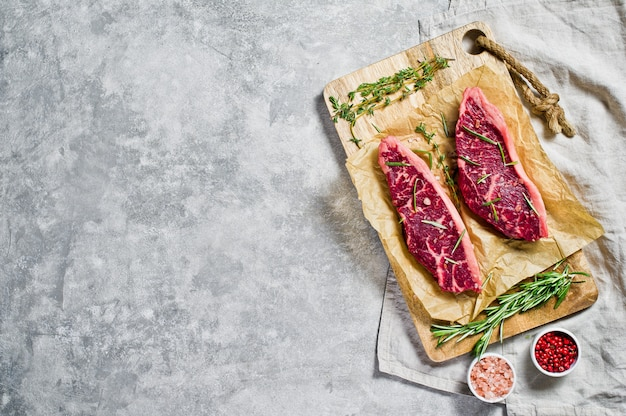 Beef sirloin steak on a wooden chopping board with rosemary and pink pepper. copyspace