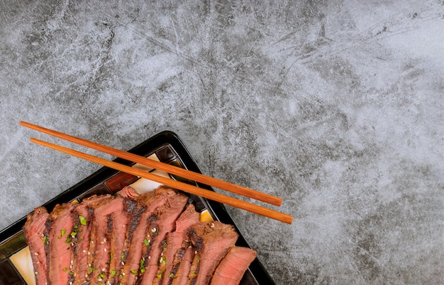 Beef sliced with chopstick on black plate.