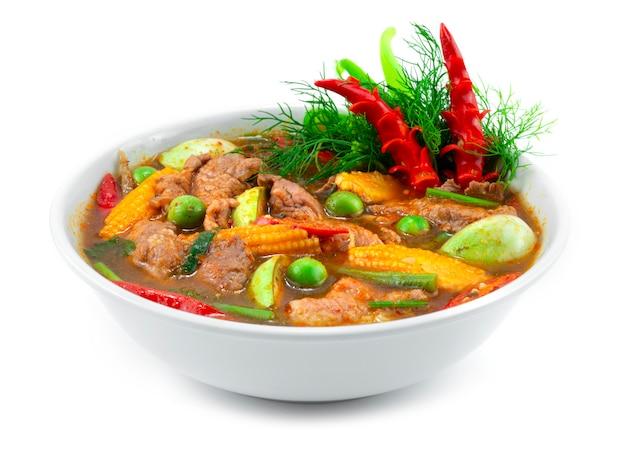 牛肉のスパイシーなレッドカレーの春のスープとハーブのタイ料理ローカルスタイルは、唐辛子と野菜のサイドビューを彫って飾る