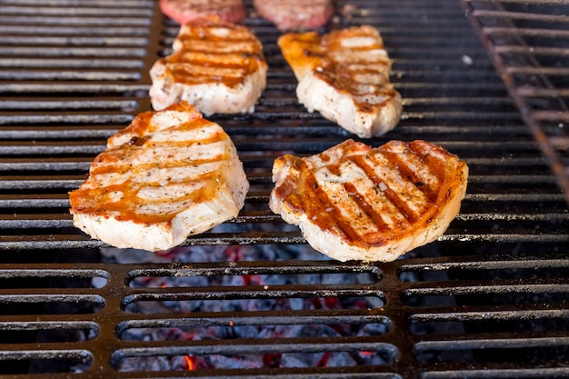 Beef steak cooking over flaming grill.grilled meat skewers, barbecue.delicious cooked meat. garden party.pork steak