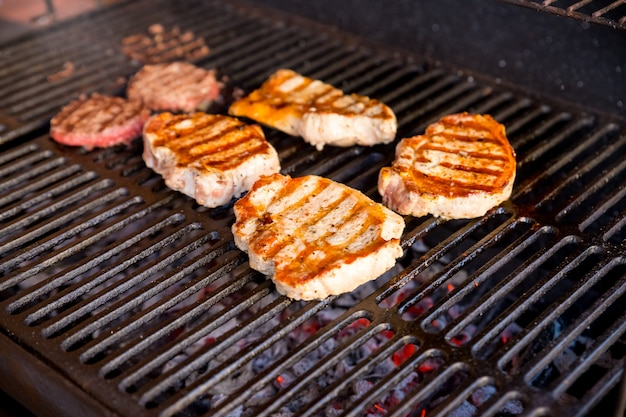 Beef steak cooking over flaming grill.grilled meat skewers, barbecue.delicious cooked meat. summer season. party.pork steak