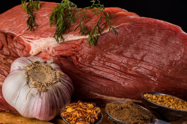 Beef steak on cutting board accompanied by onion, garlic and some various spices