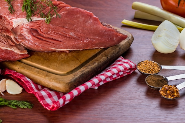 Beef steak on cutting board accompanied by onion, garlic and various spices