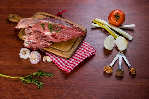 Beef steak on cutting board accompanied by onion, tomato, garlic and various spices