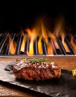 Beef steak on the cutting board with grill with fire background. brazilian barbecue.