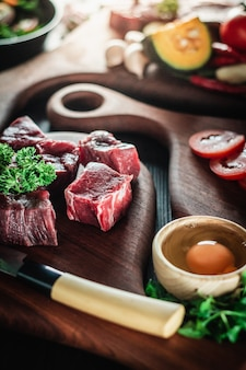 Beef steak on a cutting board with a knife and ingredients