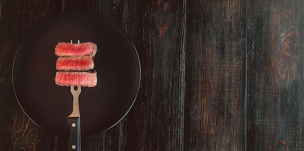 Beef steak on a fork on a dark wooden surface