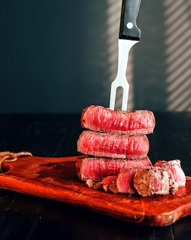 Beef steak on a fork on a dark wooden surface
