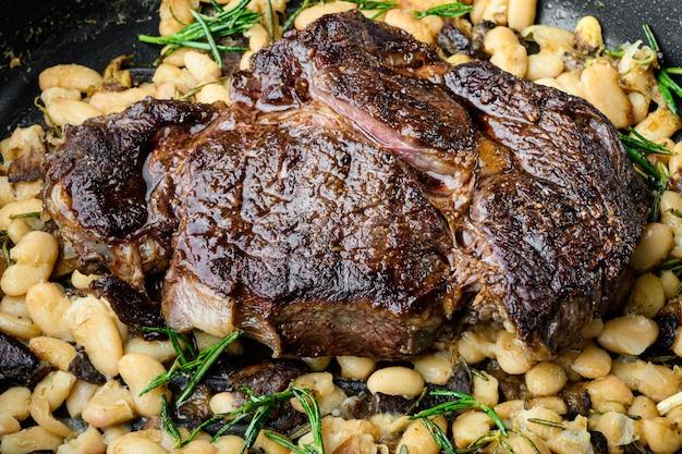 Стейк из говядины на гриле с розмарином, фасолью и специями, на чугунной сковороде, на черном камне