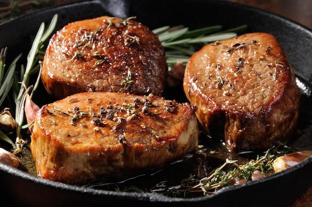 Стейк из говядины. сочный средний стейк рибай дольки зелень специи