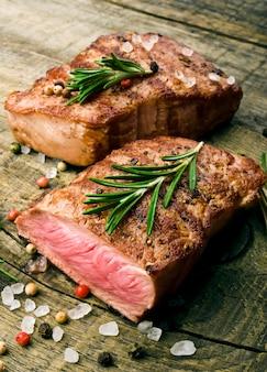 Стейк из говядины на деревянном столе.