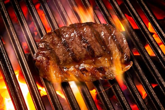 Стейк из говядины на гриле с огнем. бразильское барбекю.