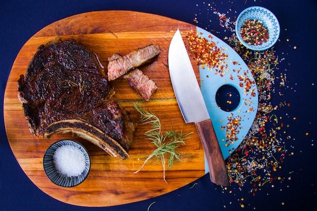 木の板に牛肉のステーキ、塩、コショウ、ローズマリー。リブアイステーキ。