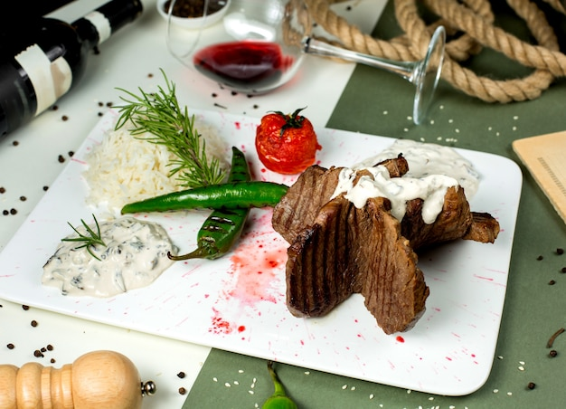 Beef steak pieces served with creamy mushroom sauce rice and grilled vegetables