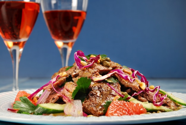 Beef steak salad with glasses of wine