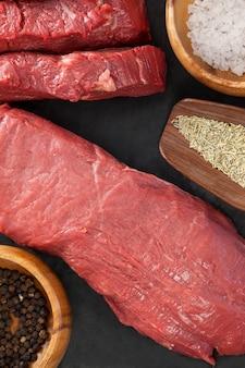 Стейк из говядины, соль и специи на черной грифельной тарелке