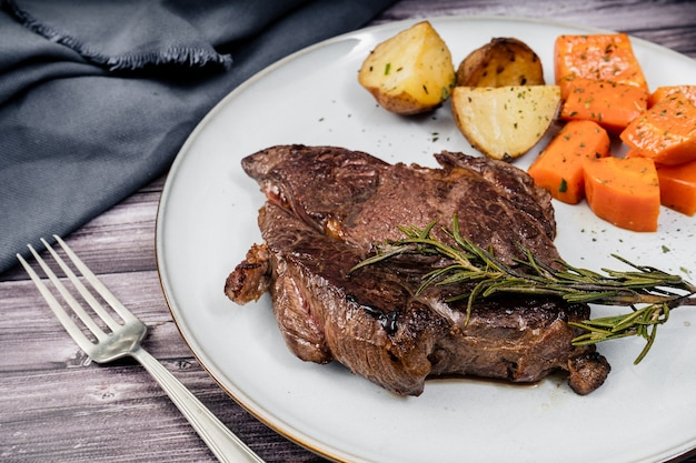 Beef steak served on a plate with rustic potatoes and carrots on a wooden table. 45 degree view
