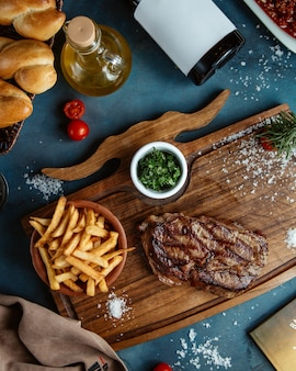 Beef steak served with french fries and diced gren herbs on wooden board