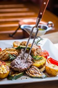 ステーキ。サーロインステーキ。フォークに美味しいジューシーなビーフステーキ。野菜のグリル