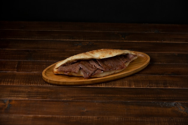 Beef steak slices in bread on wood serving plate