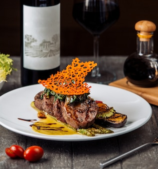 Beef steak slices garnished with herbs and sauce, served with grilled vegetables