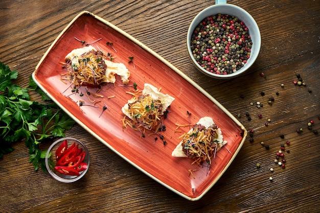 쇠고기 스테이크 타르타르는 나무 바탕에 빨간 접시에 크루통에 재직했습니다. 레스토랑 음식.