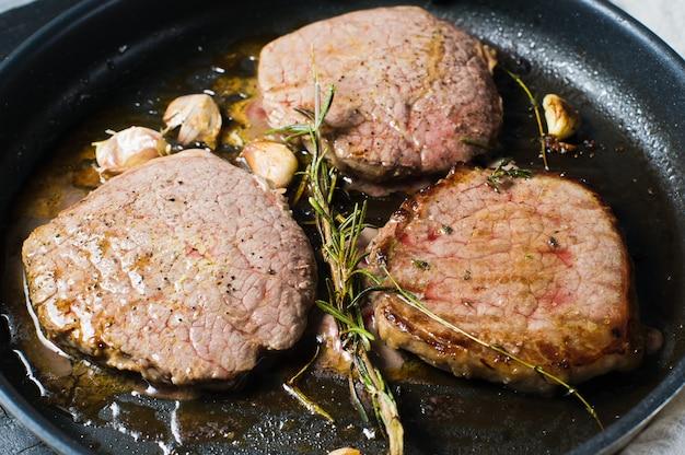 Beef steak tenderloin in the pan, cooking.