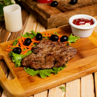 Beef steak thin served with ketchup mayonnaise and vegetable salad.