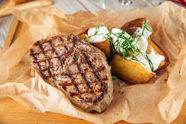 Стейк из говядины с запеченным картофелем со сметаной