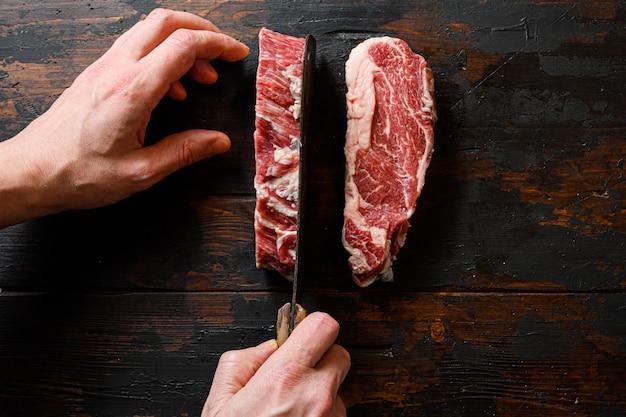 Стейк из говядины руками мясника и нож для мяса на работе отбивная