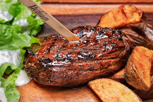 Beef steak with french fries and lettuce on a wooden board.