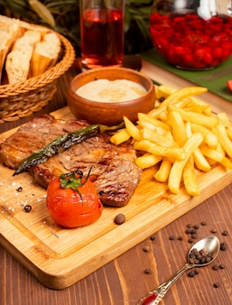 Beef steak with french fries, sour cream mayonnaise sauce and herbs on wooden plate.
