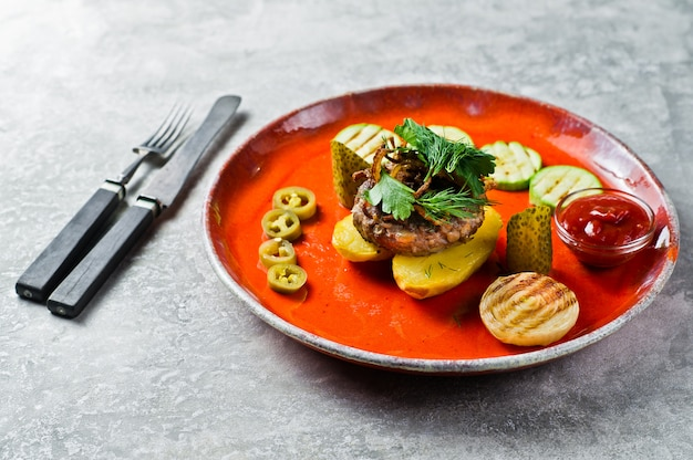 Beef steak with grilled vegetables, zucchini, onion, bell pepper.