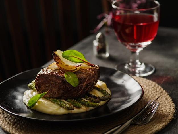 Стейк из говядины с картофельным пюре и спаржей на черной тарелке. ужин в ресторане.