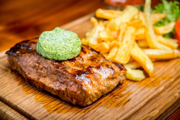 Beef steak with pepper sauce and grilled vegetables on cutting board