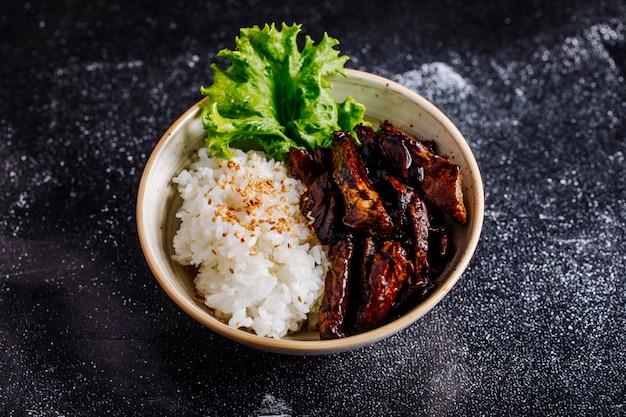 Стейк из говядины с рисовым гарниром и листьями салата внутри белой чаши.